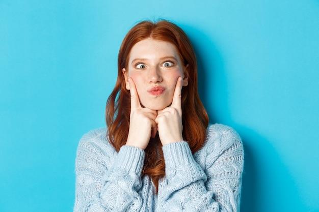 Primo piano di una ragazza adolescente dai capelli rossi divertente che fa smorfie, strizza gli occhi e colpisce le guance, in piedi su sfondo blu