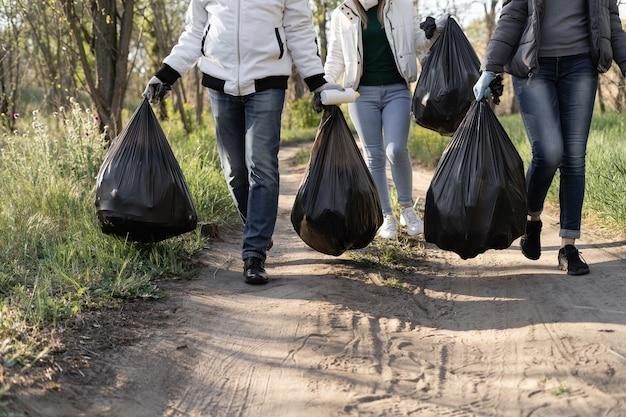 Primo piano dei sacchi della spazzatura nelle mani dei volontari. giornata della terra e concetto di pulizia del parco.