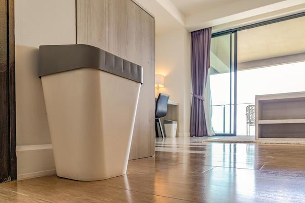 Close up immondizia spazzatura cestino di plastica può con coperchio grigio nella camera da letto del resort con la luce della finestra dietro.