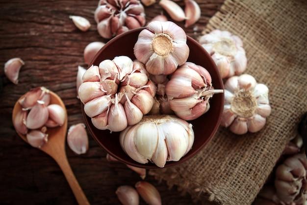 Chiuda sulla lampadina dell'aglio in ciotola sulla tavola di legno, colpo sopraelevato superiore