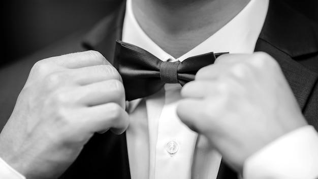 Close-up di gentiluomo regolazione farfallino.
