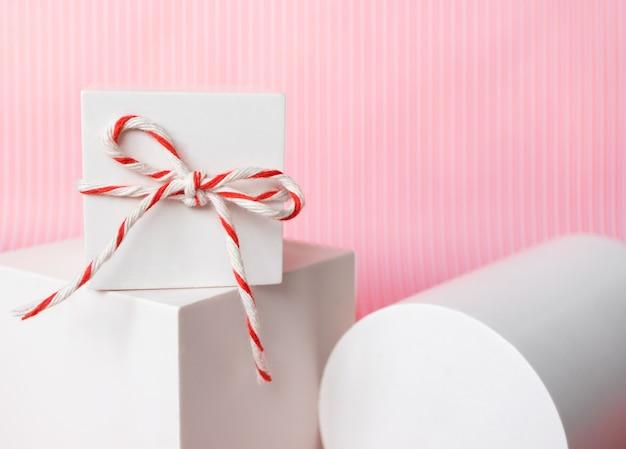 Confezione regalo in primo piano con corda di cotone spago a strisce bianche rosse e oggetti di forma geometrica astratta