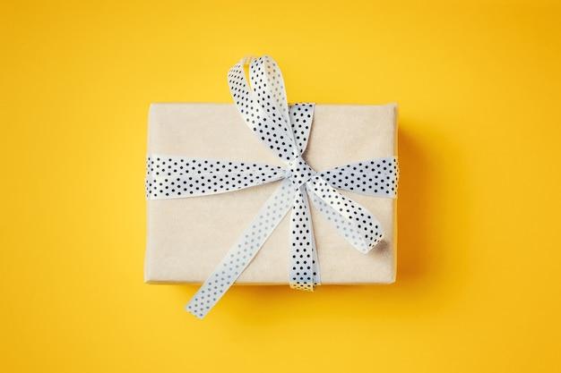 Chiuda sul contenitore di regalo con il nastro bianco su un fondo giallo, vista superiore