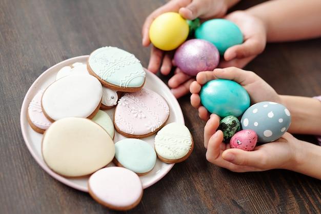 Primo piano di torte di panpepato sul piatto con uova di pasqua nelle mani dei bambini per le vacanze di pasqua