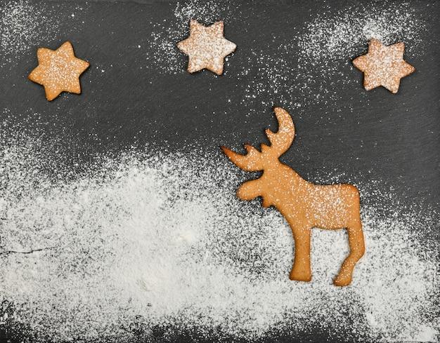 Close up biscotti di panpepato con renne di natale su sfondo nero ardesia con glassa di zucchero bianco in polvere e spazio copia, vista dall'alto in elevazione, direttamente sopra