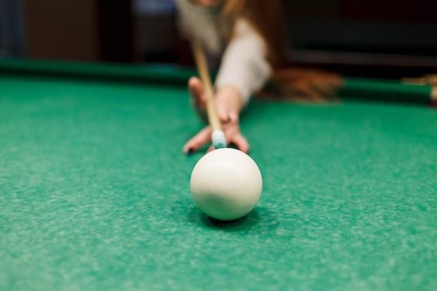 Primo piano alla ragazza che mira una stecca su una palla in un tavolo da biliardo