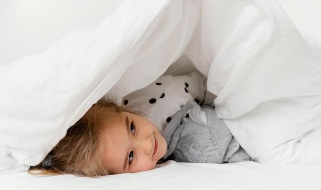 Ragazza del primo piano che si nasconde sotto la coperta