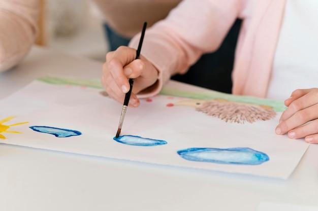 Ragazza del primo piano che dipinge le nuvole blu