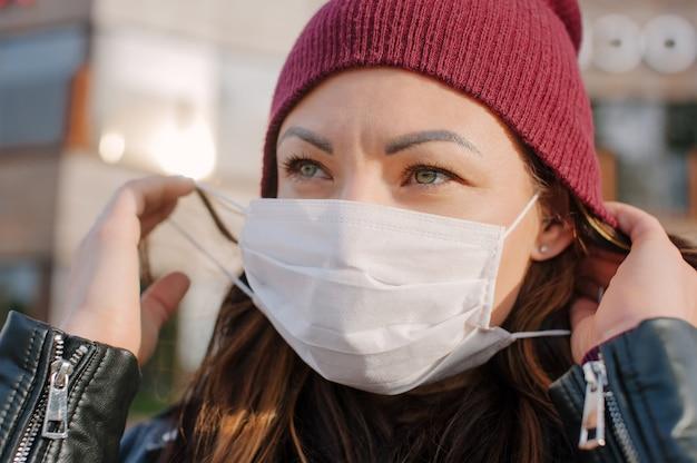 Primo piano di una ragazza che indossa una maschera medica sul viso. sullo sfondo di un business center in vetro.