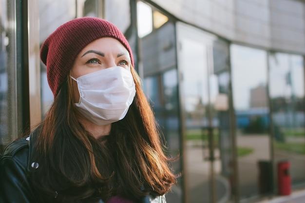 Primo piano del viso di una ragazza in una maschera medica. sullo sfondo di un edificio di vetro.