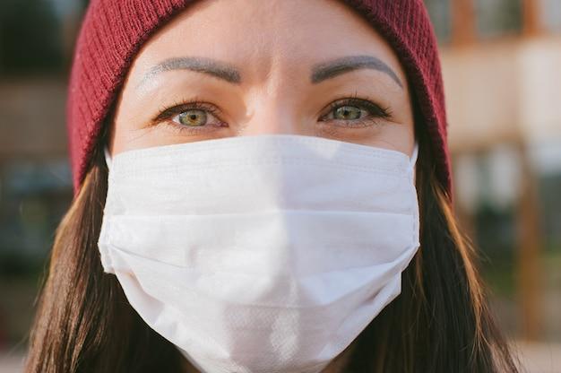Primo piano del viso di una ragazza in una maschera medica.
