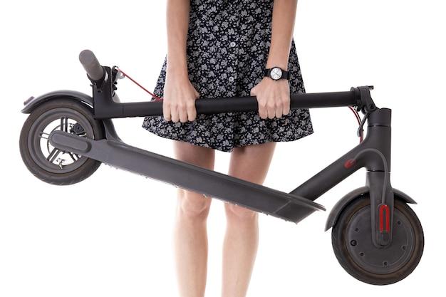 Primo piano della mano di una ragazza che tiene uno scooter elettrico piegato su sfondo bianco