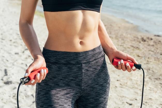Primo piano di una ragazza con una pancia piatta con una corda per saltare nelle sue mani sulla spiaggia