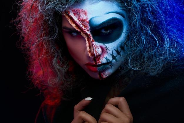 Chiuda in su della ragazza con trucco di halloween che indossa il mantello nero