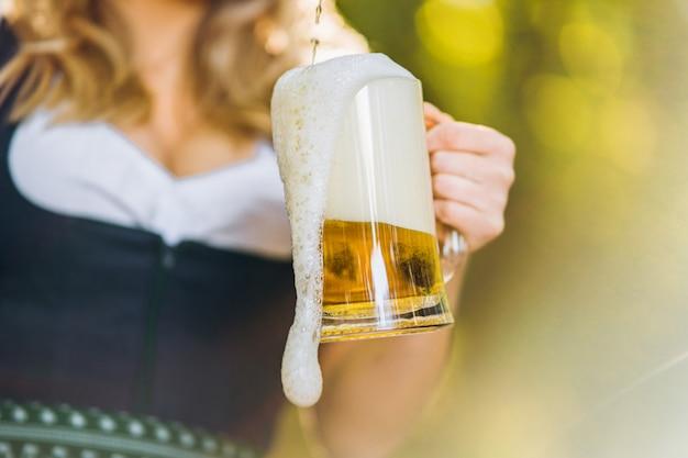 Primo piano delle mani delle ragazze in dirndl versando un bicchiere pieno di birra con schiuma enorme all'aperto