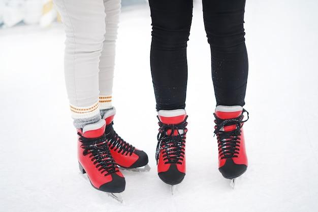 Primo piano delle ragazze in piedi in pattini rossi sull'arena del ghiaccio