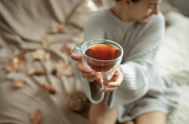 Primo piano di una tazza di tè di vetro su uno sfondo sfocato in mani femminili.