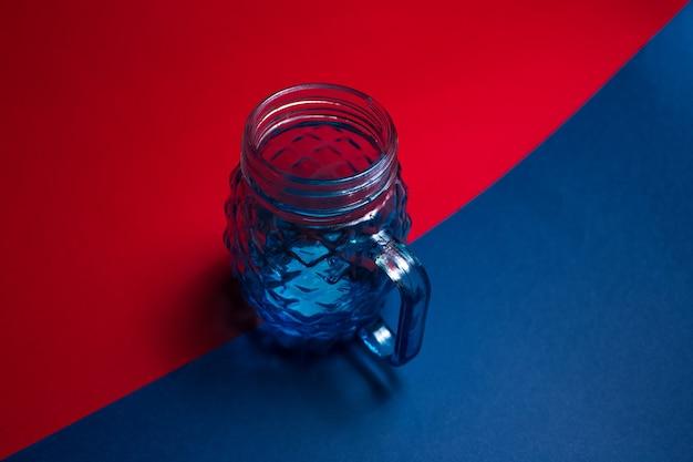 Primo piano della tazza di vetro per il succo sulla superficie scura di colore rosso e blu