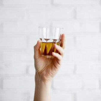 Primo piano di un bicchiere di whisky o succo di mela in mano maschile su sfondo bianco muro di mattoni