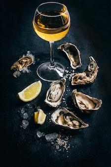 Primo piano di un bicchiere di vino bianco con ostriche e limone su sfondo nero
