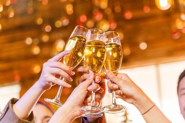 Chiudere i bicchieri di bicchieri di champagne tintinnanti con festa di illuminazione con bere champagne