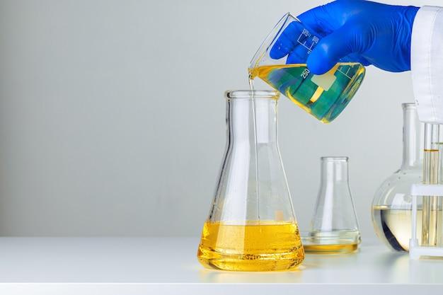 Chiuda in su delle mani guantate di uno scienziato che lavora con campioni di laboratorio
