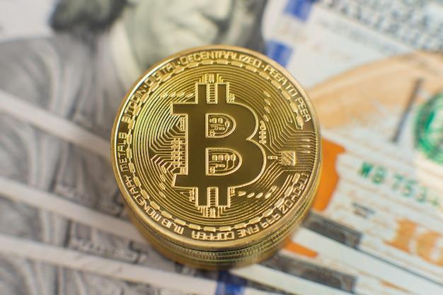 Primo piano di bitcoin oro in piedi di fronte a banconote da un dollaro