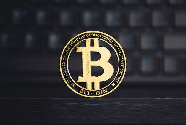 Primo piano di bitcoin d'oro sul tavolo di legno con uno sfondo sfocato della tastiera