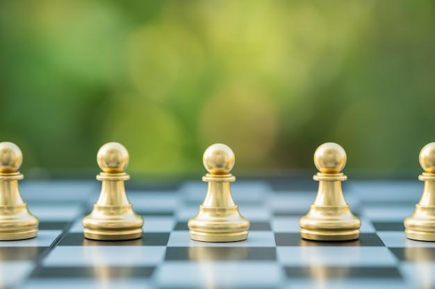 Chiuda in su degli scacchi del pedone d'oro sulla scacchiera