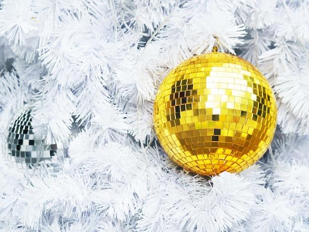 Chiuda sulle palle dorate di scintillio sul pino bianco dell'abete con lo spazio della copia.