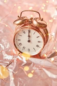 Chiuda sulla sveglia dipinta d'oro con il tempo di natale è mezzanotte su uno sfondo astratto dorato lucido con ghirlanda di luci, spazio di copia.