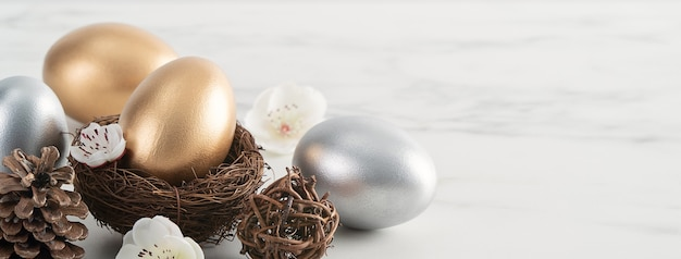 Chiuda in su delle uova di pasqua d'oro e d'argento nel nido con il fiore di prugna bianco sul fondo della tavola in legno bianco brillante
