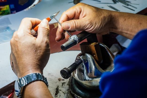 Chiuda in su della mano di un orafo che fa l'anello d'argento.