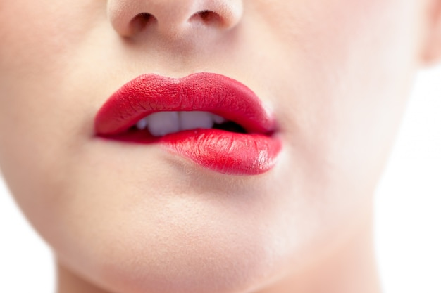Chiuda in su sul modello splendido che morde le labbra rosse