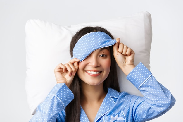 Primo piano della splendida giovane ragazza asiatica in pigiama blu, maschera per dormire al decollo per sbirciare qualcosa di interessante con un sorriso felice, sdraiato sul cuscino a letto, svegliarsi con sorpresa, sfondo bianco.