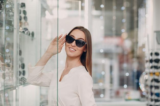 Chiuda in su della splendida giovane donna sorridente sorridente raccogliendo e scegliendo gli occhiali all'angolo dell'ottico presso il centro commerciale. bella donna felice l'acquisto di occhiali da vista dall'ottico optometrista