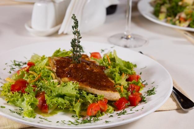Close up gourmet appetitoso piatto principale carnoso su lattuga fresca e pomodori. servito in tavola al ristorante.