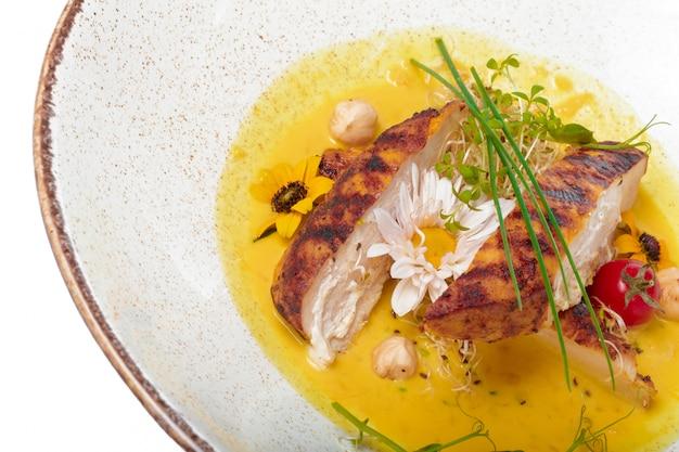 A ravvicinata di un piatto gourmet con petto di pollo alla griglia