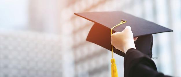 Close up laureato in mano tenere spettacolo cappello in edificio scolastico sfondo. colpo del tappo di laurea durante il diploma universitario di inizio, concetto di apprendimento del successo dello studente di educazione.
