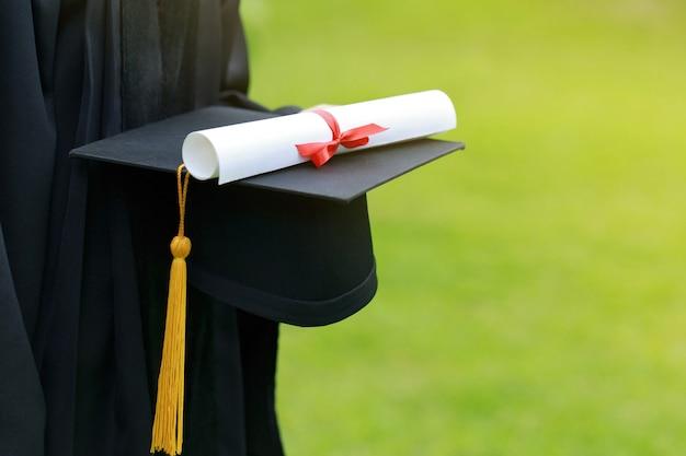 Primo piano laureato in possesso di un cappello concetto educazione di successo all'università con spazio copia