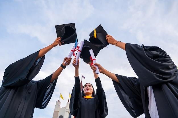 Primo piano di laureati che tengono in mano cappelli e diplomi