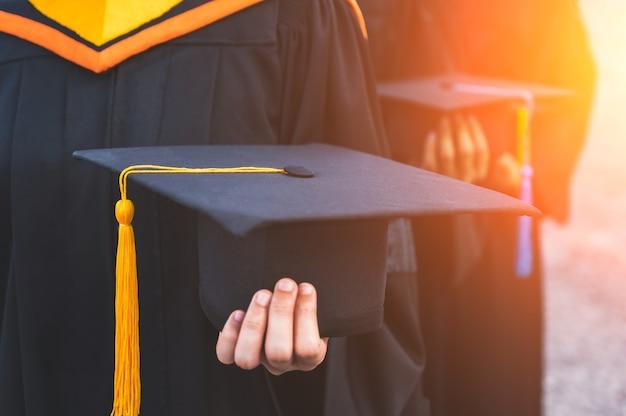 Primo piano di laureati che tengono in mano i cappelli