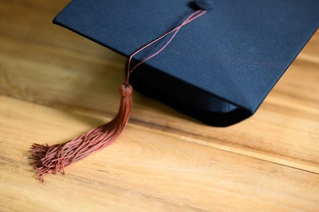 Primo piano del berretto di laurea sulla scrivania in legno