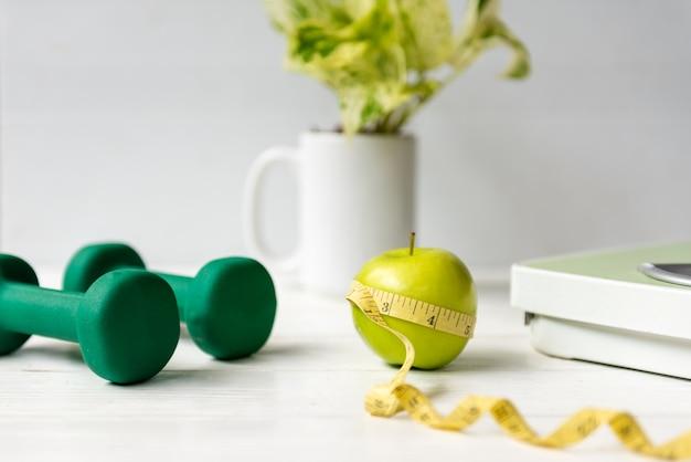 Chiuda sulla mela verde con nastro adesivo di misurazione. piano di salute dietetica. la nutrizione avvia la pianificazione dell'allenamento