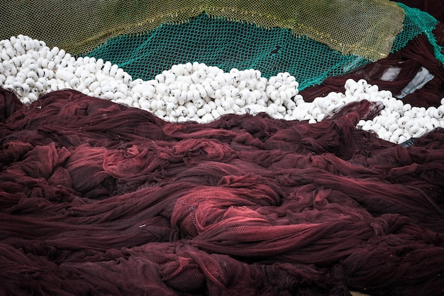 Close-up di reti da pesca verdi e marroni e trappole essiccazione sulla costa galiziana al tramonto