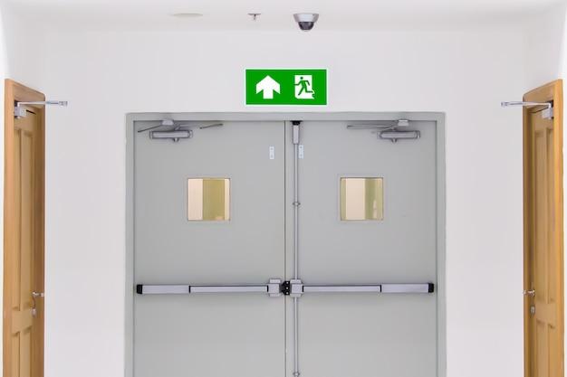 Chiudi il cartello verde dell'uscita antincendio con l'uscita della porta.