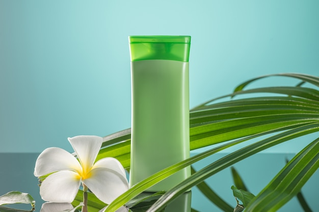 Primo piano: gel doccia biologico verde e fiore di plumeria, con foglie verdi su sfondo verde