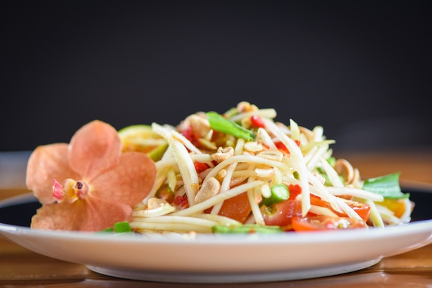 Close up di insalata di papaya verde piccante cibo tailandese sul fuoco selettivo tavolo - som tum thai asian food - insalata di papaya servita sul piatto