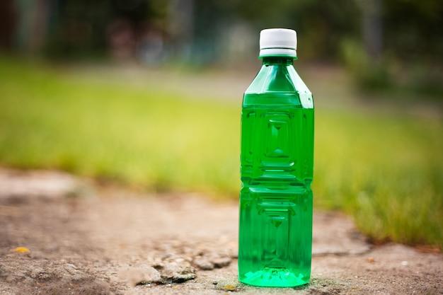 Primo piano della bottiglia di plastica verde su sfondo sfocato all'aperto.
