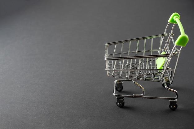 Close-up di carrelli della spesa verde su sfondo nero. concetto di vendita. carrello, prodotti, copia spazio. vista laterale
